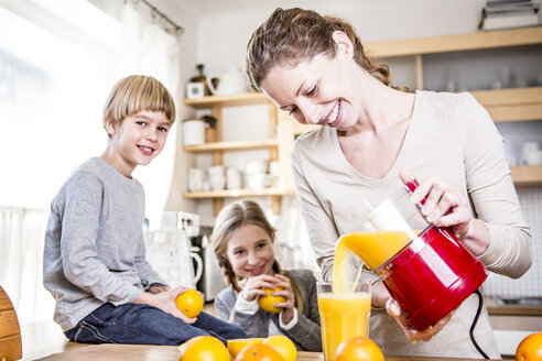 Woman pouring freshly squeezed orange juice into glass for children - WESTF23012