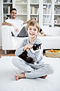 Smiling boy caressing cat at home - WESTF23036