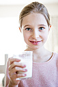 Portrait of smiling girl holding glass of milk - WESTF23054