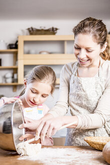 Mother and daughter baking in kitchen together - WESTF23060