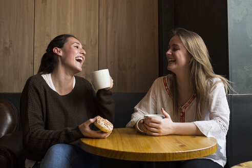 Two laughing friends in a coffee shop - ABZF01967