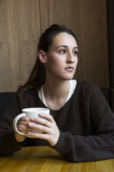 Portrait of serious woman with cup of coffee in a coffee shop - ABZF01970