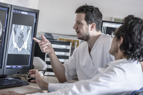 Two doctors discussing x-ray image on computer screen - MWEF00155