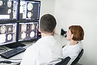 Two doctors discussing x-ray images on computer screen - MWEF00164