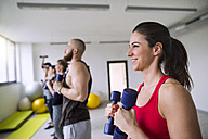 Group of athletes exercising with dumbbells in gym - HAPF01608