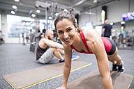 Portrait of smiling young woman exercising in gym - HAPF01611