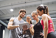 Group of happy athletes with tablet after exercising in gym - HAPF01617