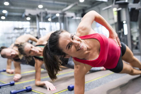 Portrait of smiling young woman exercising in gym - HAPF01626