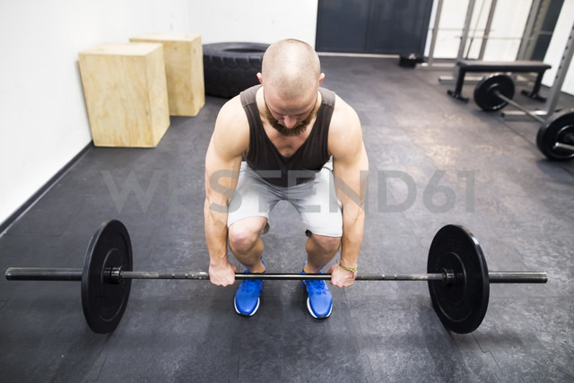 Young man preparing to lift barbell - HAPF01632 - HalfPoint/Westend61
