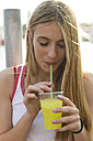 Young woman drinking yellow beverage - KKAF00726