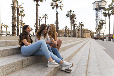 Spain, Barcelona, three happy young women sitting on stairs having fun - KKAF00738