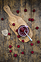Spoon and jar of raspberry jam and raspberries on wood - LVF06065