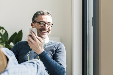 Portrait of smiling businessman using smartphone and earphones - UUF10492