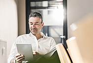Content businessman sitting in his office using tablet - UUF10501