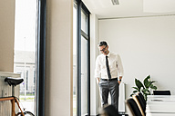 Laughing businessman standing in conference room - UUF10507