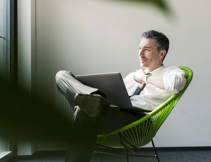 Smiling businessman with laptop sitting in an armchair - UUF10510