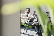 Smiling businessman sitting in an armchair with tablet using smartphone and earphones - UUF10513
