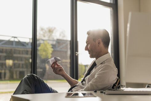Businessman sitting at desk in his office looking at paper plane - UUF10525