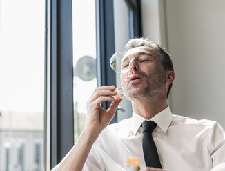 Businessman blowing soap bubbles - UUF10528