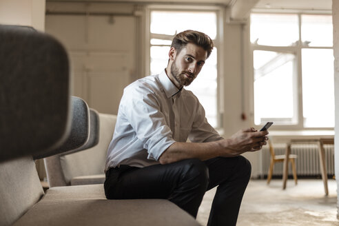 Portrait of young businessman using cell phone in a loft - JOSF00733