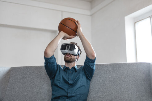 Young man with basketball sitting on couch using Virtual Reality goggles - JOSF00739