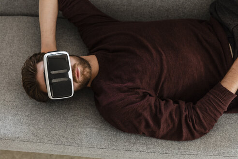 Man lying on the couch using Virtual Reality Glasses - JOSF00754