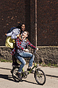 Young man riding bicycle with his girlfriend standing on rack - UUF10548