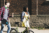 Young couple with bicycle and skateboard walking in the street - UUF10551