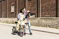 Young couple with bicycle and skateboard taking smartphone selfies - UUF10554