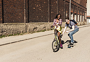 Young woman on bicycle pulling young man, standing on skateboard - UUF10557