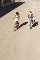 Happy couple running and biking in the street - UUF10560