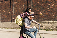 Young couple riding bicycle in the street, woman standing on rack, taking selfies - UUF10563