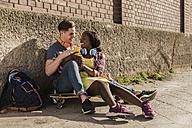 Young couple sitting on ground, usind smartphone - UUF10566