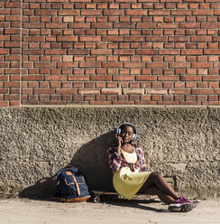Young woman sitting on ground, listening music with headphones - UUF10569
