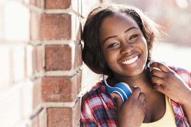 Portrait of a happy young woman with headphones around her neck - UUF10572