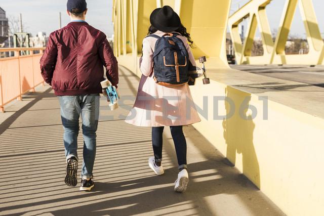 Young couple with skateboard walking on bridge - UUF10575 - Uwe Umstätter/Westend61