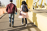 Young couple with skateboard walking on bridge - UUF10575