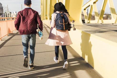 Young couple with skateboard walking on bridge - UUF10575