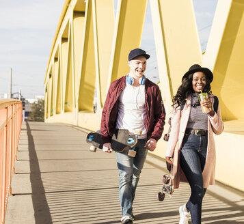 Young couple with skateboard walking on bridge - UUF10578