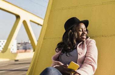 Young woman sitting on  bridge using smartphone - UUF10584