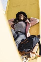 Young woman sitting on  bridge - UUF10587