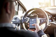 Man in car adjusting devices at home via smartphone - NAF00083