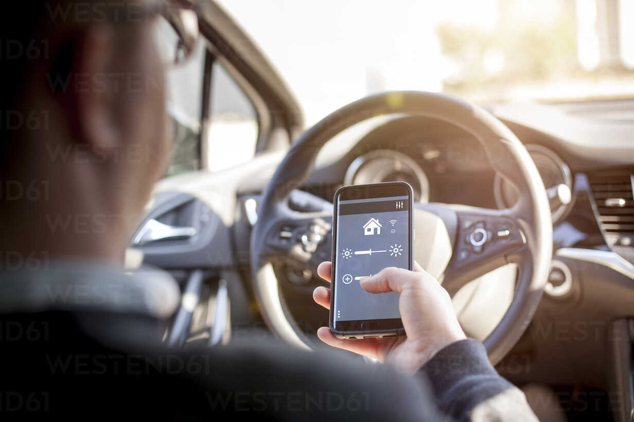 Man in car adjusting devices at home via smartphone - NAF00083 - sinanmuslu/Westend61