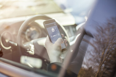 Man in car adjusting devices at home via smartphone - NAF00086