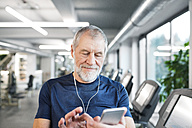 Senior man with smartphone and earphones in gym - HAPF01650
