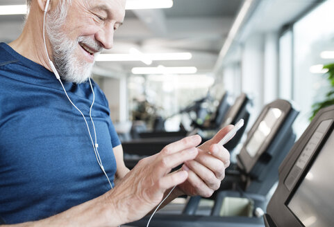Senior man with smartphone and earphones in gym - HAPF01653