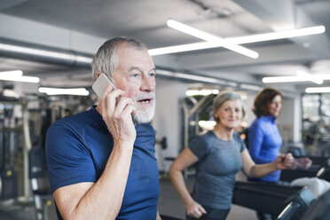 Group of fit seniors working out on treadmills in gym, man with smart phone - HAPF01656
