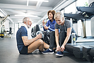Group of fit seniors in gym resting after working out - HAPF01659