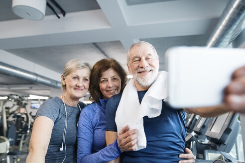 Group of fit seniors in gym taking a selfie with smartphone after working out - HAPF01662