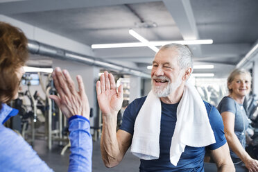 Happy senior man and woman high fiving after working out in gym - HAPF01665